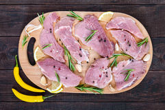 Raw flat meat for steak chop with spices on a cutting board on a dark wooden table. Stock Photos