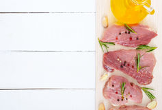 Raw flat meat for steak chop with spices and oil on a white wooden background. Royalty Free Stock Images