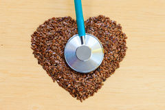 Raw flax seeds heart shaped and stethoscope Royalty Free Stock Photo