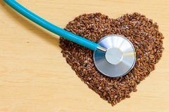 Raw flax seeds heart shaped and stethoscope Royalty Free Stock Photography