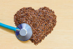 Raw flax seeds heart shaped and stethoscope Stock Photography