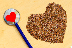 Raw flax seeds heart shaped and stethoscope Stock Images