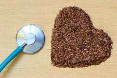 Raw flax seeds heart shaped and stethoscope Royalty Free Stock Image