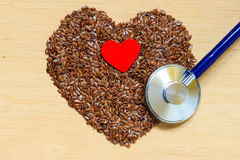 Raw flax seeds heart shaped and stethoscope Stock Photo