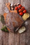 Raw flounder with ingredients on a table. vertical top view. Raw flounder with ingredients on a cutting board on a table. vertical top view Royalty Free Stock Photos