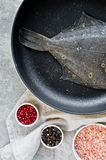 Raw flounder in the pan. Gray background, top view. royalty free stock images