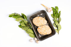 Raw food, chicken cutlet ready for prepare. With bay leaves. Minced chicken portion in plastic box on white background Royalty Free Stock Image