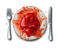 Raw Food. Concept as a squashed tomato on a dinner plate with a fork and knife with juice splattered as a metaphor for creative cuisine and cooking with passion Royalty Free Stock Photos