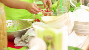 Raw food festival. Middle aged woman placing  fresh vegetable salads on the plates Stock Photos
