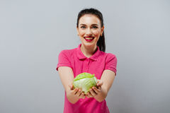 Raw food, veggie concept. Portrait of smiling good looking girl in casual clothing holding red cabbage in her hands over Royalty Free Stock Photography