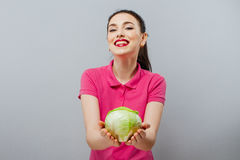 Raw food, veggie concept. Portrait of smiling good looking girl in casual clothing holding red cabbage in her hands over Stock Image