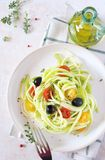 Raw foodism: uncooked spaghetti zucchini, cherry tomatoes, olives. Raw food diet: uncooked spaghetti zucchini, cherry tomatoes, olives salad and olive oil. Top Royalty Free Stock Photo