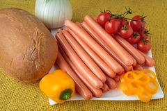 Raw frankfurter sausages and bread on plate. Raw frankfurter sausages and bread on white plate Stock Images