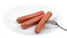 Raw frankfurter sausages on a plate isolated. Three raw frankfurter sausages on a plate isolated Stock Image