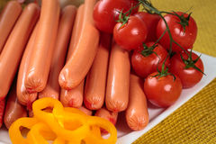 Raw frankfurter sausages on white plate. Close up of raw frankfurter sausages on white plate Stock Image