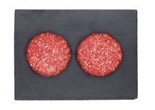 Raw fresh beef burgers on stone plate Royalty Free Stock Photography