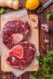 Raw fresh beef meat cross cut for ossobuco on cutting board with. Ingredients for making gremolata, top view Royalty Free Stock Photo