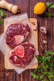 Raw fresh beef meat cross cut for ossobuco on cutting board with. Ingredients for making gremolata, top view Stock Images