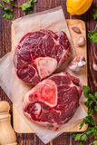 Raw fresh beef meat cross cut for ossobuco on cutting board. Raw fresh beef meat cross cut for ossobuco on cutting board with ingredients for making gremolata Royalty Free Stock Image