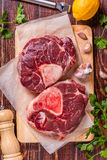 Raw fresh beef meat cross cut for ossobuco on cutting board. Raw fresh beef meat cross cut for ossobuco on cutting board with ingredients for making gremolata Stock Photos