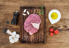 Raw fresh beef meat cross cut for ossobuco with garlic cloves, cherry tomatoes, rosemary, pepper, oil and salt on Royalty Free Stock Image
