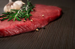 Raw fresh beef meat on a cutting board. Closeup with a sprig of rosemary, garlic and peppercorn Royalty Free Stock Image