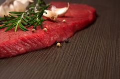 Raw fresh beef meat on a cutting board. With a sprig of rosemary, garlic and peppercorn closeup with copy space Royalty Free Stock Photos