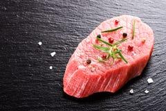 Raw fresh beef steak on dark stone background Stock Photo