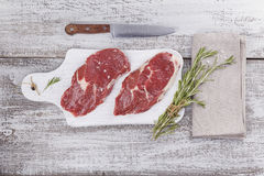 Raw fresh beef steak on a white cutting board Royalty Free Stock Images