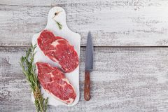 Raw fresh beef steak on a white cutting board Royalty Free Stock Image