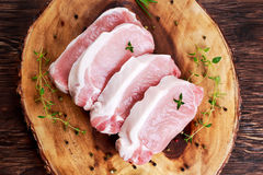 Raw Fresh Boneless Pork Chops with herbs. on wooden board. Royalty Free Stock Image
