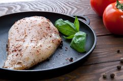 Raw fresh chicken fillet with spices and herbs and basil lies on a black iron frying pan and is ready to fry on a wooden. Brown table next to red tomatoes and Stock Photography