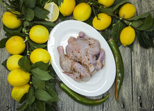Raw fresh chicken on porcelain plate with lemon and chilli  on the wooden background Stock Photos