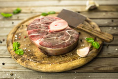 Raw fresh cross cut veal with garlic, pepper and seasonings on wooden cutting board with butcher cleaver. Eye bird view royalty free stock photo