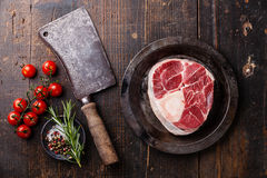 Raw fresh cross cut veal shank for making Osso Buco. And meat cleaver on dark wooden background Royalty Free Stock Image