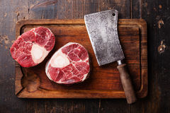 Raw fresh cross cut veal shank for making Osso Buco. And meat cleaver on wooden cutting board Stock Photography