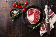 Raw fresh cross cut veal shank for making Osso Buco. And meat fork on dark wooden background Stock Images