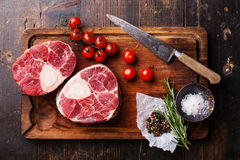 Raw fresh cross cut veal shank for making Osso Buco. Raw fresh cross cut veal shank and seasonings for making Osso Buco on wooden cutting board Stock Images