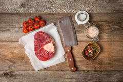 Raw fresh cross cut veal shank and meat cleaver. For making Osso Buco on wooden background, top view Royalty Free Stock Photo