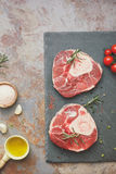 Raw fresh cross cut veal shank on a slate board. Raw fresh sliced veal shank and Ingredients for making Osso Buco on rustic background. Overhead view, vintage royalty free stock photography