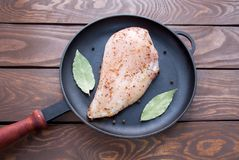 Raw fresh fillet of chicken breast with herbs and spices and bay leaf is ready for cooking, in a black frying pan made. Of iron, on a wooden table top view on Royalty Free Stock Images
