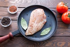 Raw fresh fillet of chicken breast with herbs and spices and bay leaf and red tomatoes is ready for cooking, in a black. Raw fresh fillet of chicken breast with Stock Photos