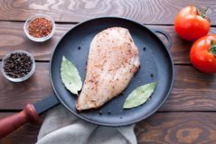 Raw fresh fillet of chicken breast with herbs and spices and bay leaf and red tomatoes is ready for cooking, in a black. Frying pan made of iron, on a wooden Stock Image