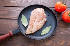 Raw fresh fillet of chicken breast with herbs and spices and bay leaf and ripe tomatoes is ready for cooking, in a black. Raw fresh fillet of chicken breast with Royalty Free Stock Photos