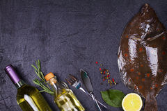 Raw fresh fish, white wine bottle, lemon and herbs on gray stone texture background. View from above, top studio shot. Stock Photos