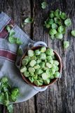 Raw fresh half cutted  brussel sprouts. On a wooden table Royalty Free Stock Images