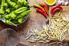 Raw fresh homemade Italian pasta on a wooden cutting board with. Food ingredients: acute ripe peppers, olive oil, garlic, basil Stock Photography