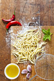 Raw fresh homemade Italian pasta on a wooden cutting board with. Food ingredients: acute ripe peppers, olive oil, garlic, basil Stock Photos