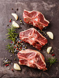 Raw fresh lamb loin chops with herbs. And spices on stone slate plate royalty free stock images