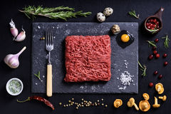 Raw fresh lamb meat with condiments, cooking ingredients. Raw fresh lamb meat with condiments, cooking ingredients on black background. Top view, flat lay Stock Image